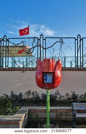 Tulip Shaped Public Phone In Front Of Grunge Wall With Metal Fence And On Background Of Flag Of Turk