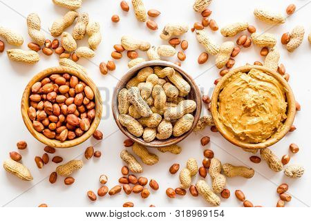 Product For Hearty Breakfast With Peanut Butter In Bowl Near Nuts On White Background Top View Patte