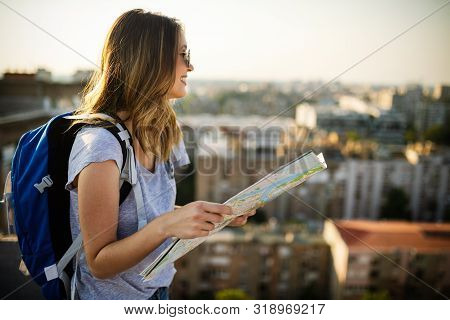 Happy Female Tourist Searching Road To Hotel On Map In City During Vacation