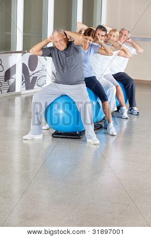 Senior citizens doing back exercises on gym ball in gym