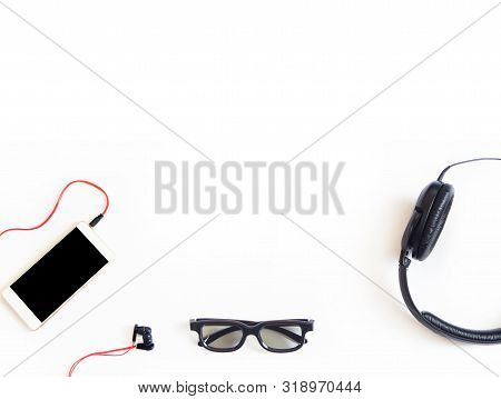 Flat Lay. Smartpnone, Headphones And Glasses On White Background. Music, Gadgets And Technology Conc