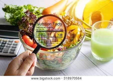 Nutritional Information Concept. Hand Use The Magnifying Glass To Zoom In To See The Details Of The