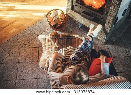 Boy Sitting In Comfortable Armchair In Cozy Country House Near Fireplace And Enjoying A Warm Atmosph
