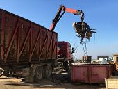 A grapple truck loads scrap industrial metal for recycling. poster