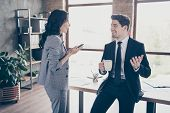 Photo of two business people having coffee break standing workstation communicating dressed formal wear suits poster