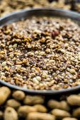 Mandvi pak, sing pak, chiki, peanut barfi or chikki in a silver colored plate along with roasted peanuts and some raw also on the wooden surface. poster