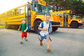Two Funny Happy Caucasian Boys Students Kids Running Near Yellow Bus On 1 September Day. Education A