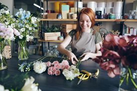 Cheerful beautiful redhead florist in apron standing at table with tender flowers and arranging bouquet in flower shop