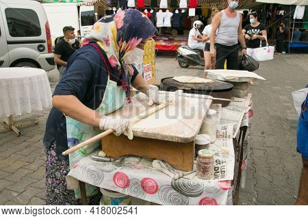 Alanya , Turkey- October 20, 2020: Unidentified Woman with protective mask  prepares pita bread on the street market in Alanya, Turkey. Pita bread with cottage cheese and greens.