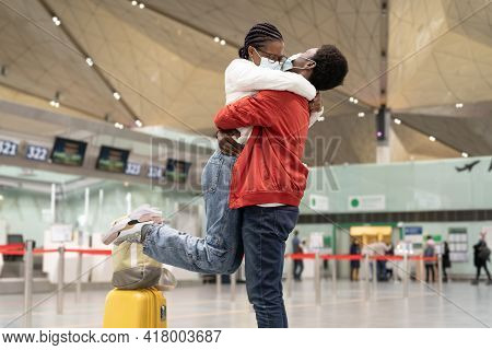 African Couple Reunion Under Covid-19 New Normality. Cheerful Man And Woman In Medical Masks Hug In