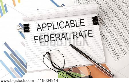 Notebook With Text Applicable Federal Rate On The Table With Charts,pen And Glasses.