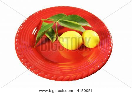 Freshly Picked Lemons With Leafs Attached On A Plate