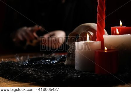 Soothsayer At Table Indoors, Focus On Skull And Candles
