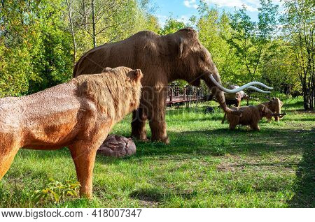 Russia, Moscow - September 29, 2018: Ice Age Hunting. A Prehistoric Lion Attacks A Herd Of Mammoths