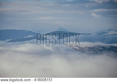 Awesome Mountain Landscape With Sharp Snowy Mountain Peak On Horizon Above Clouds. Atmospheric Minim
