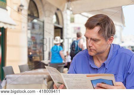 Caucasian European Male Tourist Looking At Menu Of Outdoor Dining Italian Restaurant