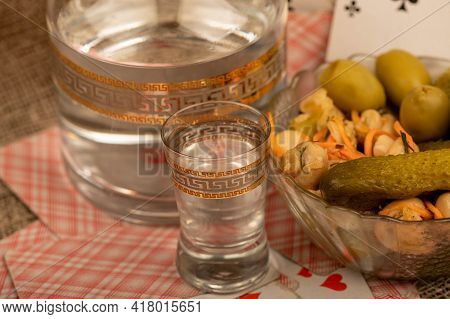Playing Cards, A Glass Of Vodka, A Decanter Of Vodka And A Glass Dish With Pickles And Mushrooms On