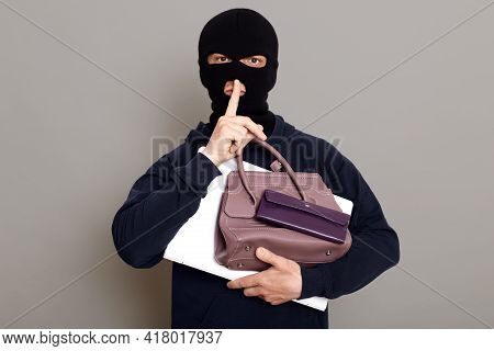 Man Burglar Holds Laptop, Wallet And Woman's Purse In His Hands, Holds Finger To His Mouth, Shows Ge