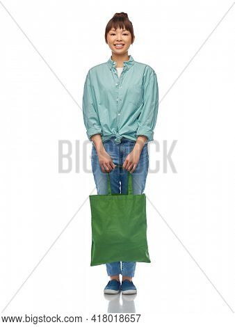 sustainability and people concept - happy smiling young asian woman in turquoise shirt and jeans with green reusable canvas bag for food shopping over white background