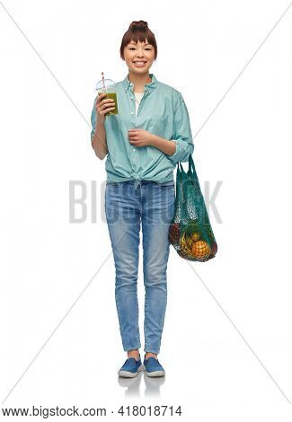 healthy eating and sustainability concept - asian woman drinking green smoothie from plastic cup and holding reusable string bag with fruits and vegetables over white background