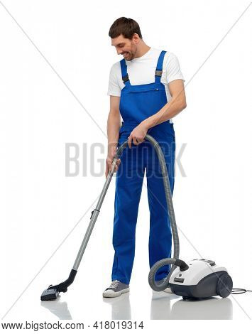 profession, service and people concept - happy smiling male worker in overall cleaning floor with vacuum cleaner over white background