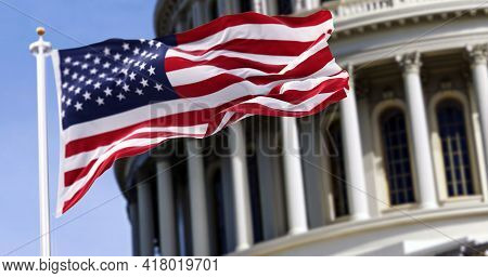 The Flag Of The United States Of America Flying In Front Of The Capitol Building Blurred In The Back