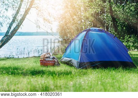 Tourist Tent Under Near Lake In Forest At Sunrise. Summer Outdoor Landscape.