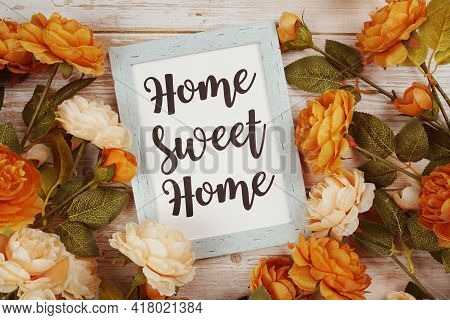 Home Sweet Home Typography Text With Flower Decoation On Wooden Background