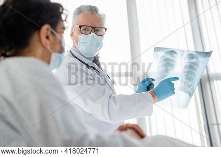 Radiologist In Eyeglasses And Medical Mask Pointing At Lungs X-ray Near African American Woman On Bl