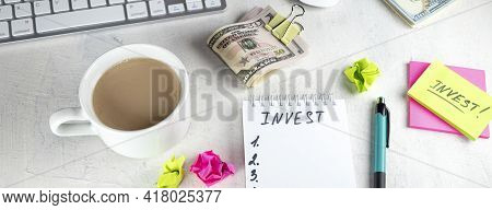 Banner With Invest Written In Notebook, Wad Of Dollars Money Cash In Elastic Band Copy Space Backgro