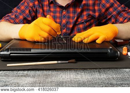A Computer Repair Technician Disassembles A Laptop For Further Cleaning Or Repair. Service Of Person