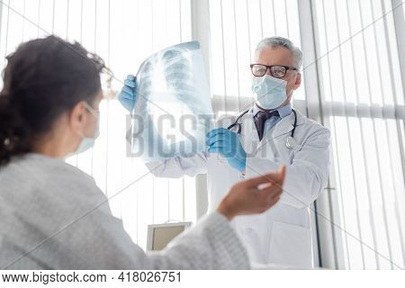 Radiologist In Medical Mask Holding Lungs X-ray Near African American Woman On Blurred Foreground.