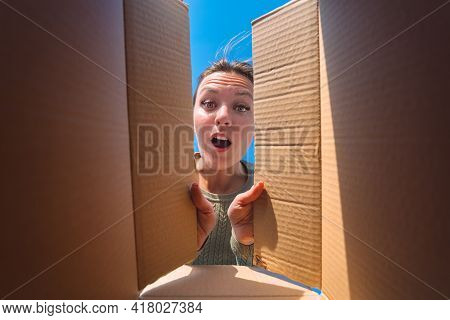 Surprised Woman Unpacking Cardboard Box. Satisfied Woman Unboxing Delivery Package. View From The Bo