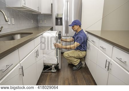 Repairman Installing A Dishwasher In A Modern Style Kitchen