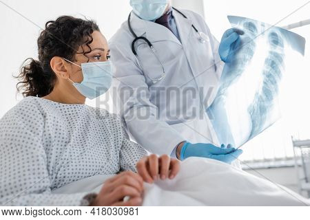 Radiologist In Latex Gloves Showing Lungs X-ray To African American Woman In Medical Mask, Blurred F