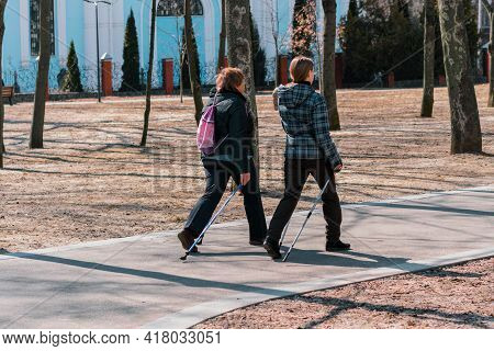 Two Woman Walks Together In The Park Using Tourists Sticks. Back View. Strolling Through The Pathway