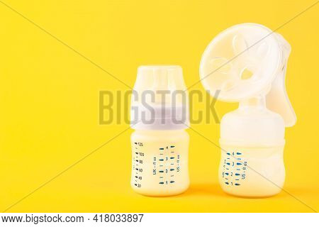 White Plastic Baby Bottle With Pacifier,breast Pump Rich In Baby Food, On Yellow Background. Copy Sp