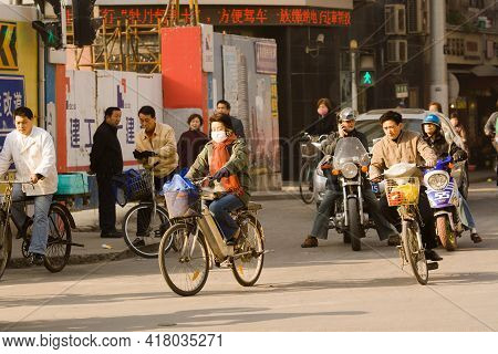 Shanghai, China, Asia - November 20, 2008: Woman Riding A Bicycle With Face Mask In The Chaotic Traf