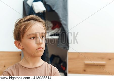 Boy Standing Near Messy Clothes On Shelf. Preteen Boy With Dirty Clothing In His Room. Messy Home Ki