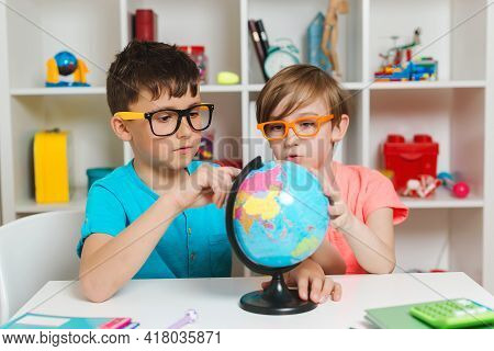 School Kids Studying A Globe. Education And Geography. Back To School. Smiling Students Looking At G