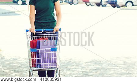 Woman Pushing Shopping Cart At Parking. Female After Shopping Going To The Car. Big Summer Sale. Sho