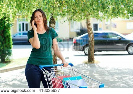 Woman Talking By Mobile Phone At The Parking Place. Woman Pushing Shopping Cart Near Supermarket. Fe
