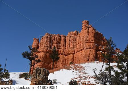 A Beautifully Colorful Full Frame Panorama Of Red Cliffs Contrasting With Green Conifers And Snow Ag