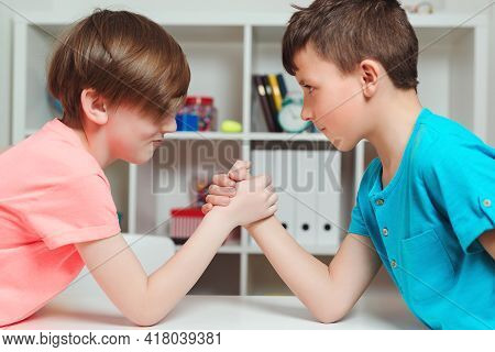 Cute Boys Competing In Arm Wrestling During The Break Time. Happy Friends Playing Arm Wrestle Lookin