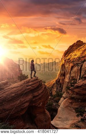 Adventurous Woman At The Edge Of A Cliff Is Looking At A Beautiful Landscape View In The Canyon. Sun