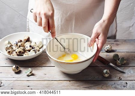 Female Hands Whipping Quail Eggs In Bowl At A Wooden Table, Making Mayonnaise.