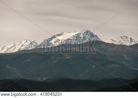 The Snow Capped Peak Of The 2389 Metre High Monte Padru In Corsica With Hills In The Foreground