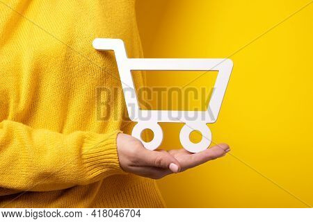 Shopping Trolley On Hand Over Yellow Background, Buying Online Concept