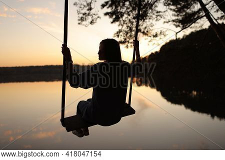 Silhouette Of A Romantic Young Woman On A Swing Over Lake At Sunset. Young Girl Traveler Sitting On
