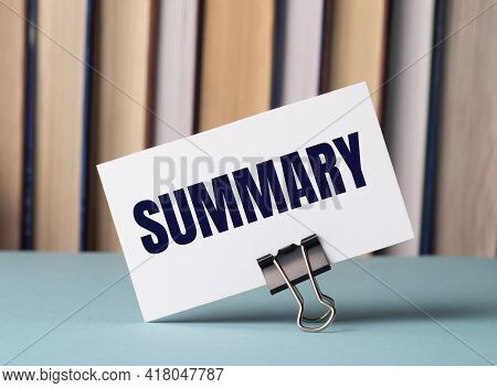 A White Card With The Text Summary Stands On A Clip For Papers On The Table Against The Background O